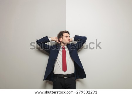 Picture of a young business man leaning on a grey wall holding both hand to his head while looking away from the camera. - stock photo