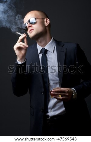 picture of a young businessman drinking and smoking