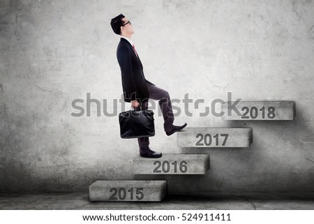 Picture of a young businessman walking upward on the stairway toward number 2017