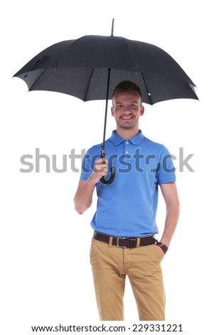 picture of a young casual man holding a black umbrella while holding his other hand in his pocket and smiling for the camera. isolated on a white background - stock photo
