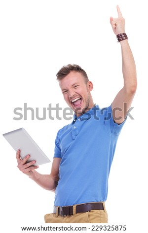 picture of a young casual man holding a tablet in a hand and cheering while looking into the camera. isolated on a white background - stock photo