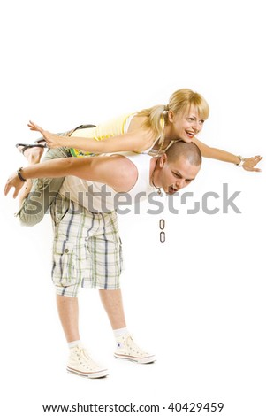 picture of a young couple having fun - woman on the back of her boyfriend, simulating flying