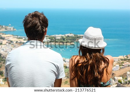 Picture of a young couple sitting side by side and looking at the blue sea. - stock photo