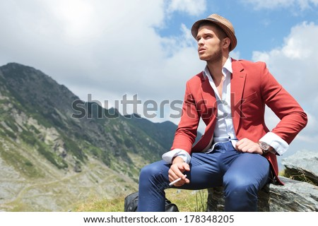 picture of a young fashion man sitting on a rock in the mountains, while looking away from the camera with a cigarette in his hand - stock photo