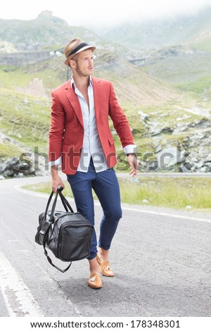 picture of a young fashion man walking on the road, in the mountains, with a bag in his hand while looking away from the camera - stock photo