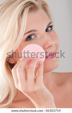 Picture of a young girl with a healthy pure skin and natural make-up cleansing her face - stock photo