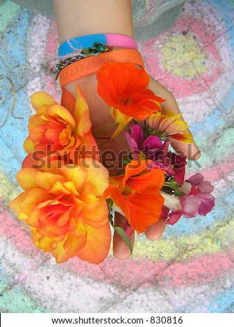 picture of a young girls hand holding several bright colored flowers