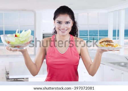 Picture of a young Indian woman compares a bowl of fresh salad and a plate of junk food