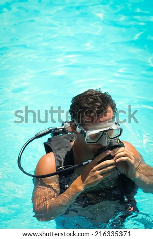Picture of a young man in a snorkelling mask in a swimming pool - stock photo