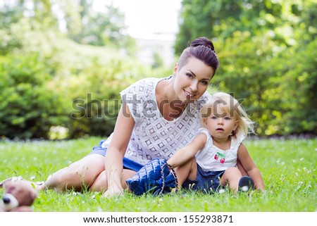 Picture of a young mother with her beautiful daughter in the park