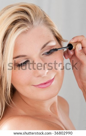 Picture of a young pretty teenage girl with a healthy skin applying her first eye make-up. Mascara