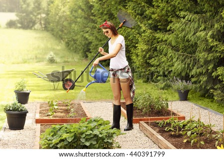 Picture of a young woman working in her garden - stock photo