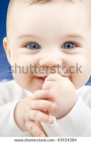picture of adorable baby face over blue sky - stock photo
