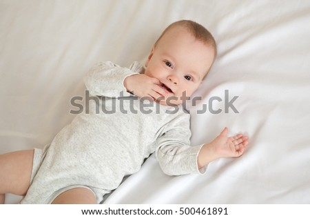 Picture of adorable baby with finger on mouth lying on bed