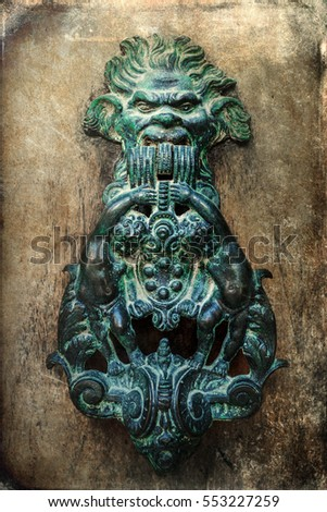 picture of an antique doorknocker on grunge texture