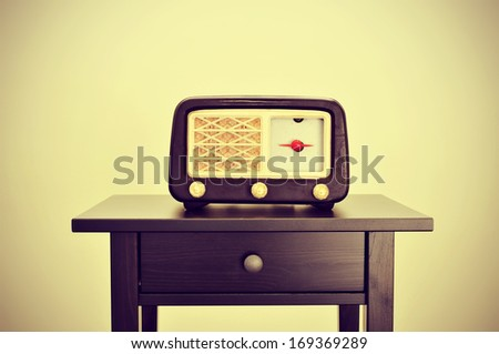 picture of an antique radio receptor on a desk, with a retro effect - stock photo