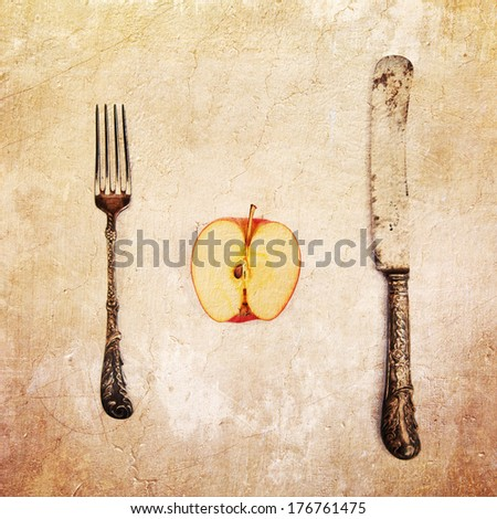 picture of an apple half with antique cutlery processed with a vintage style texture