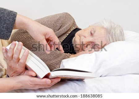 Picture of an elderly woman reading a book - stock photo
