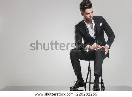 Picture of an elegant young man in tuxedo sitting on a stool, looking away from the camera while holding one hand on his knee. - stock photo
