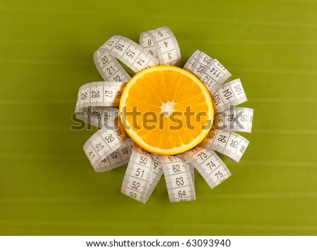 Picture of an orange and tape measure on the green background - stock photo