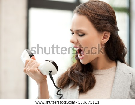 picture of angry businesswoman shouting at phone - stock photo