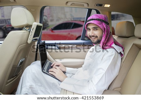 Picture of Arabic businessman working in the car with a laptop and smiling at the camera - stock photo