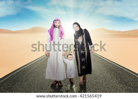 Picture of Arabic family smiling at the camera while holding hands together and walking on the street at desert - stock photo