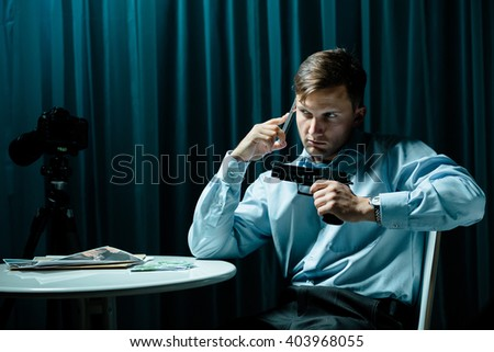 Picture of armed hitman with phone waiting for order - stock photo