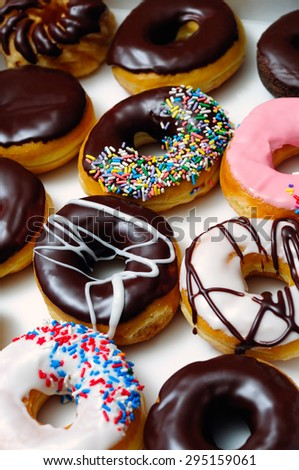 Picture of assorted doughnuts with chocolate frosted, pink glazed and sprinkles donuts. - stock photo