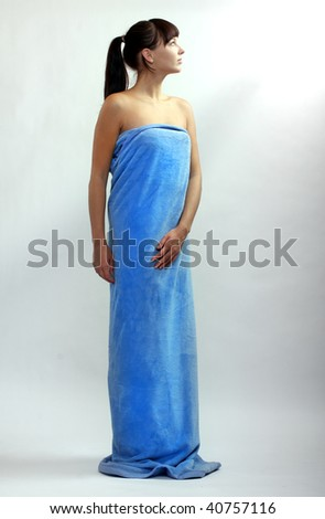 Picture of attractive beautiful woman dressed in blue towel. Studio shot. - stock photo