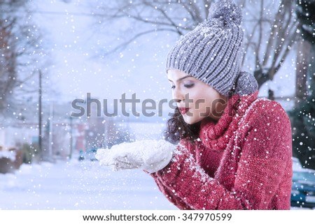 Picture of attractive indian woman wearing winter clothes playing and blowing snow on her palm, shot at the park - stock photo