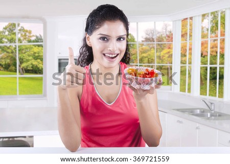 Picture of attractive young woman showing thumb up while holding a bowl of fresh tomato in the kitchen - stock photo