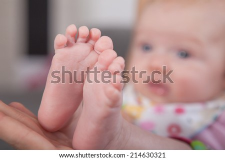 Picture of baby feets .Focus on the feets . Baby in Background unsharp. - stock photo