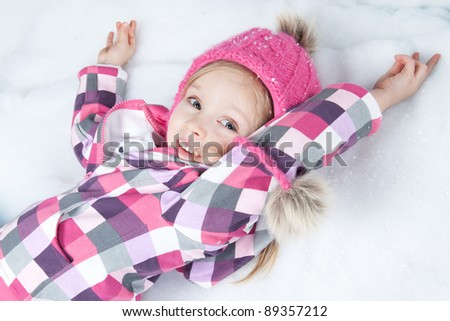 Picture of beautiful blonde little girl in pink hat lying on snow - stock photo