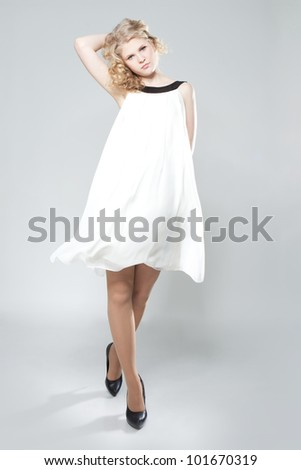 Picture of beautiful blonde teenage girl in white dress over gray