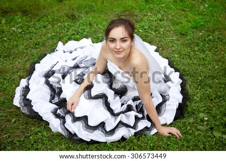 Picture of beautiful bride in white and black wedding dress lying on the grass - stock photo