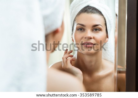 Picture of beautiful brunette looking at herself in the mirror - stock photo
