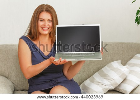 Picture of beautiful businesswoman holding laptop computer in front of her and smiling for camera. Pretty lady sitting on couch at home. - stock photo