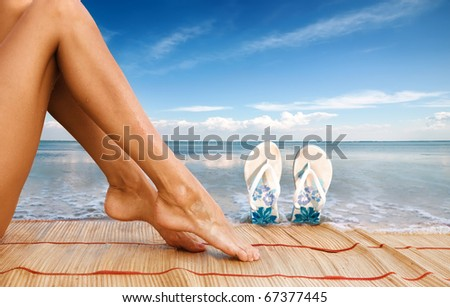 Picture of beautiful female legs and sandshoes on sea background - stock photo
