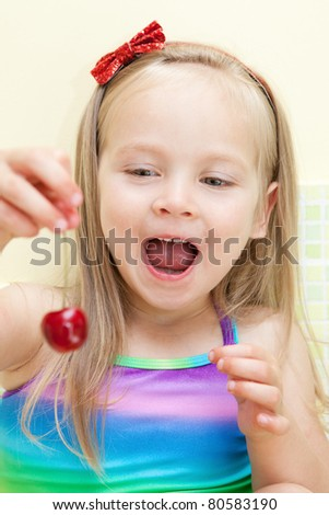 Picture of beautiful little girl eating cherry in the kitchen - stock photo