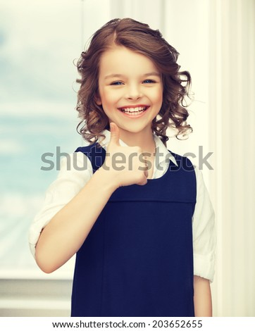 picture of beautiful pre-teen girl showing thumbs up - stock photo