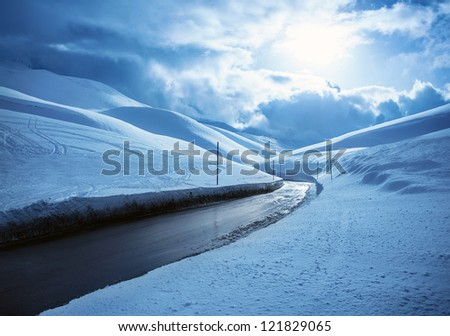Picture of beautiful snowy highway, black clean asphalt road in mountains covered white snow, wintertime weather, blue cloudy sky, cold frosty day, Christmas vacation, landscape of driveway - stock photo