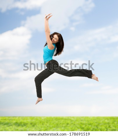 picture of beautiful sporty woman jumping in sportswear - stock photo