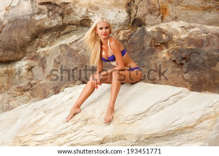 picture of beautiful tanned blonde in blue bikini sitting on the rock - stock photo