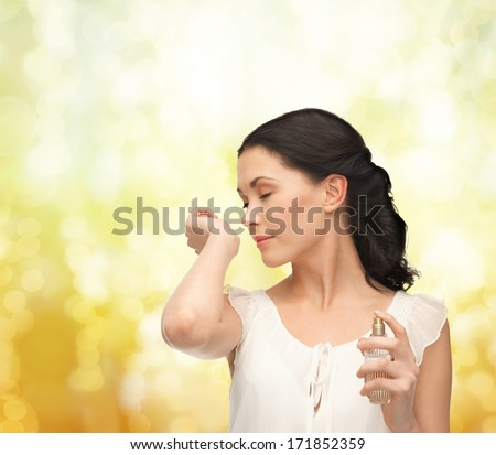 picture of beautiful woman smelling pefrume on her hand - stock photo