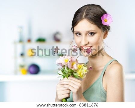 picture of beautiful woman with flowers in the kitchen - stock photo
