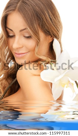 picture of beautiful woman with orchid flower in water - stock photo