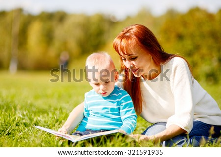 Picture of beautiful woman with son sitting down on green grass field and read fairytale in park - stock photo
