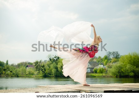 Picture of beautiful young lady in light dress dancing at water side on sun rays blue sky outdoors background - stock photo
