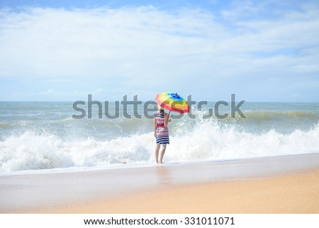 Picture of beautiful young lady with rainbow umbrella walking on sunny seashore. Backview of pretty girl standing beside waves on blurred summer outdoor background. - stock photo